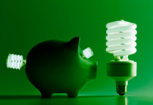 Piggy bank with fluorescent light bulbs on green background, studio shot